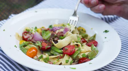 горох : A man eats a meal of pasta with cherry tomatoes and fresh peas on a striped napkin outside
