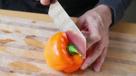 pimentas : An older man struggles to cut a bell pepper in half Stock Footage