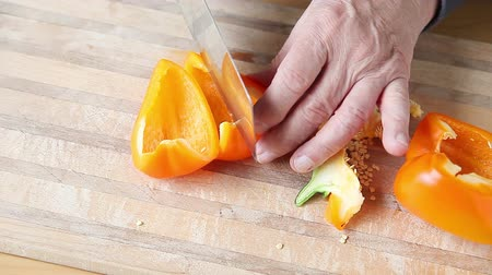 klíring : A man cleans off a cutting board, and cuts up a bell pepper