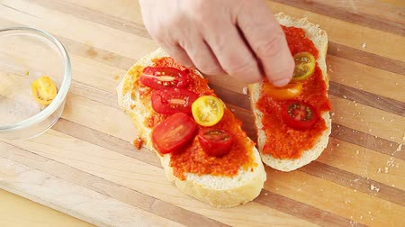 A man adds cherry tomato halves to bruschetta