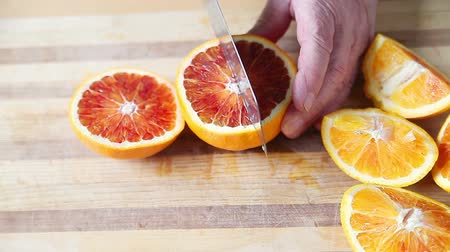 A man prepares blood oranges on a cutting board