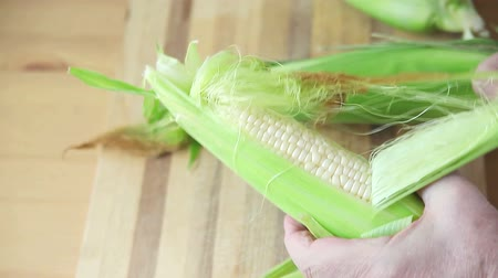 An older man pulls husk from corn on cutting board