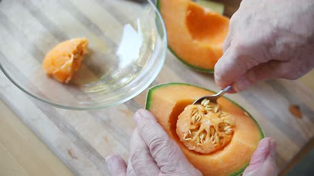 Scooping seeds from cantaloupe piece with a spoon Stock mozgókép