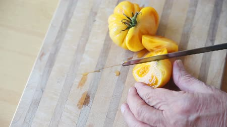 A man cuts up a ripe tomato with room for text