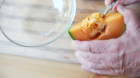 A man uses a spoon to remove seeds from cantaloupe Stock mozgókép