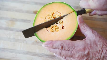 A man cuts up a cantaloupe on a cutting board Стоковые видеозаписи