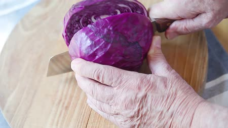 A man cuts a fresh red cabbage in two on a wood cutting board Стоковые видеозаписи