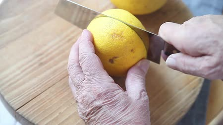 Senior man cuts a fresh grapefruit in two Стоковые видеозаписи