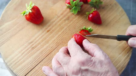 An older man cuts up a fresh strawberry on wood cutting board