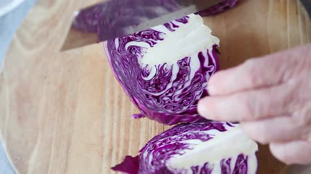 Overhead of man cutting through a red cabbage with copy space