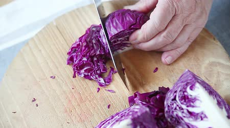 Overhead view of a man slicing cabbage for coleslaw Stock mozgókép
