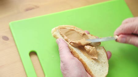 fıstık : Older man putting peanut butter on a slice of bread over a green cutting board Stok Video