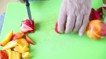 Front view of man slicing a strawberry with nectarine slices on cutting board