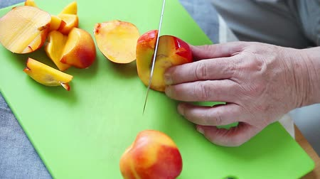 Older man cuts up a nectarine on a green cutting board