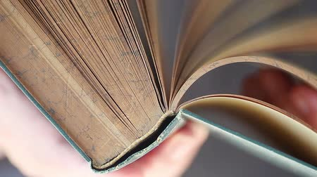 A man flips through pages in a vintage book closeup Стоковые видеозаписи