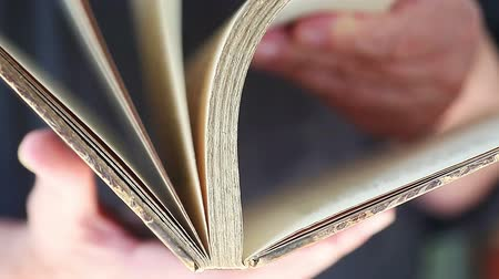 Closeup view of man flipping through pages of an old book