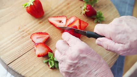 A man prepares a strawberry on a wood cutting board Stock mozgókép