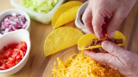 Older man prepares a taco with tomatoes, onions, lettuce, ground beef and grated cheese