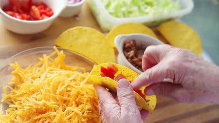 grated : A man spoons ground beef into a taco shell with grated cheese, chopped tomatoes, onions and lettuce on the cutting board beneath