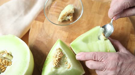 A man uses a spoon to scoop melon seeds