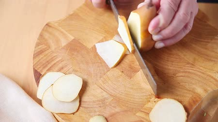 A man uses a kitchen knife to cut a fresh pear into thin slices