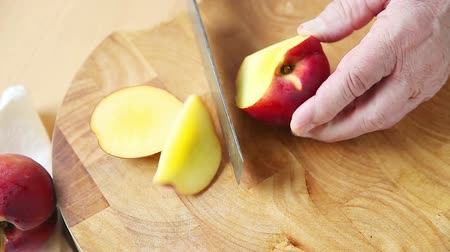 A man cutting a fresh peach on a cutting board with room for text Стоковые видеозаписи