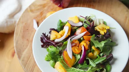 An older man adds tomatoes and red onion to a salad of mixed greens