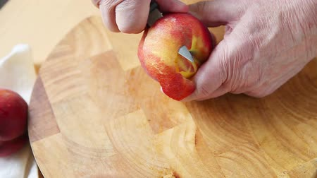 Older man peeling a peach over a cutting board with copy space Stock mozgókép