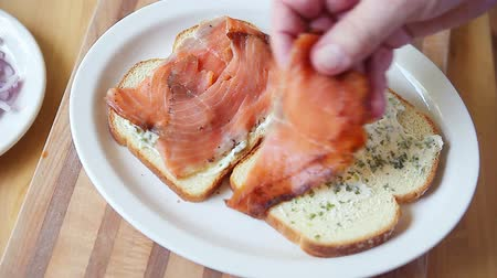 A man puts thin slices of smoked salmon on bread spread with herb mayonnaise