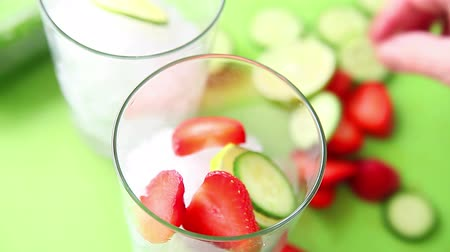 Putting cucumber and strawberry slices on crushed ice and adding water Стоковые видеозаписи