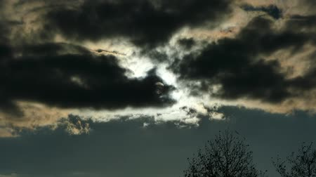 The sun is behind black clouds. Full moon