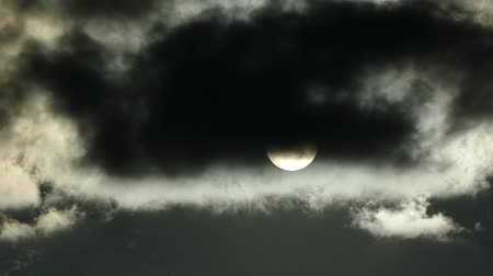 luar : The sun is behind black clouds. Full moon