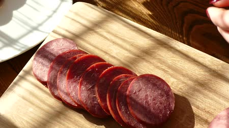 изделия из дерева : Slicing sausage on a cutting board. Beef sausage. Cut with a kitchen knife.
