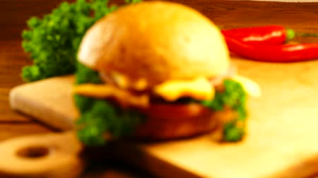 apetite : Appetizing sandwich is prepared on a cutting board. Bun, salad, parsley, sausage and cheese are cut into a sandwich.