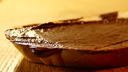 hazelnuts : Chocolate paste with a knife is smeared on a piece of white bread. To prepare a sandwich