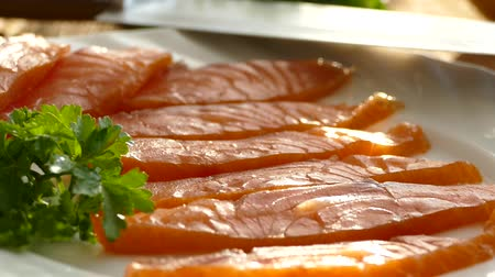 sea piece : Cut salmon fillets on a cutting board and spread on a plate. Tasty salmon fillets are sprinkled with spices. Fat Norwegian fish. Omega 3 Stock Footage