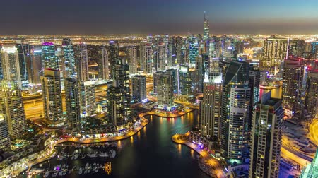 night scene : Dubai Marina with yachts in harbor and modern towers from top of skyscraper transition from day to night timelapse, Glittering lights and tallest skyscrapers during a clear evening with Blue sky. 4K Stock Footage