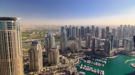 топ : Modern buildings in Dubai Marina with shadows moving very fast from morning untill evening timelapse wide angle, Dubai, UAE. . In the city of artificial channel length of 3 kilometers along the Persian Gulf 4K
