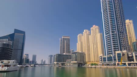 эмираты : Dubai Marina skyscrapers with yacht and boats. View from sea embankment timelapse hyperlapse at day time 4K