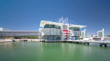 turistik : Lisbon Oceanarium, the second largest oceanarium in the world and the biggest in Europe. Parque das Nacoes. Portugal. Timelapse hyperlapse with blue sky and green water 4K