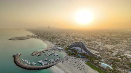 Объединенные Арабские Эмираты : Sunrise. Aerial View of Jumeirah Beach from helicopter pad Burj Al Arab at morning, Dubai, UAE timelapse wide angle lens