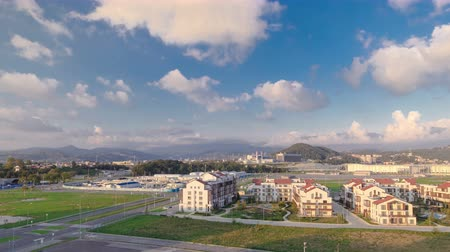 paralympics : Olympic village with stadium and mountains at the background. timelapse before sunset. Complex of dwelling-houses, where the sportsmen of the Olympic games lived 2014 year  in Sochi