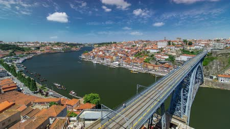 вниз : View over red roofs of the historic city of Porto, Portugal with the Dom Luiz bridge timelapse with blue cloudy sky. A metro train can be seen on the bridge Стоковые видеозаписи