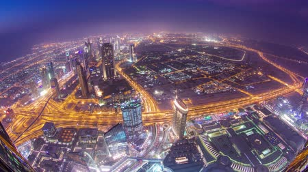 Объединенные Арабские Эмираты : Dubai downtown from day to night transition with city lights from Burj Khalifa timelapse, luxury new high tech town in middle East, United Arab Emirates architecture. View on sheikh zayed road 4K fisheye