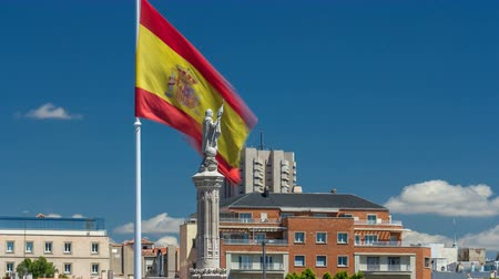 prominent : Spanish flag waves behind statue of Christopher Columbus timelapse, plaza de Colon in Madrid, Spain Stock Footage