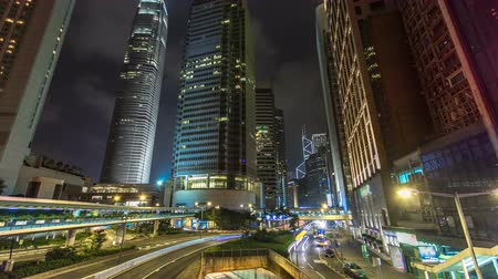 moderní : Hong Kong Business District timelapse at Night. Corporate building at the back and busy traffic across the main road at rush hour.
