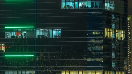 city resident : Windows in modern city office building at night timelapse.
