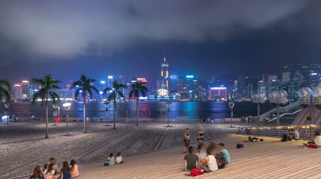 Виктория : Hong Kong city skyline at night over Victoria Harbor with clear sky and urban skyscrapers timelapse hyperlapse.