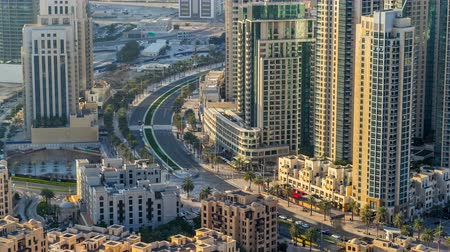 felhőkarcoló : Top view of road in Dubai downtown timelapse with day traffic and illuminated skyscrapers.