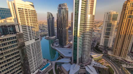 эмираты : Top view of buildings Jumeirah Lakes Towers with traffic on the road sunset timelapse.